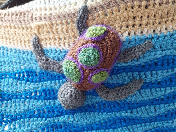 Crochet turtle on a background of white and blue, suggesting the sea.