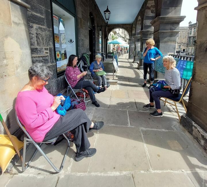 A socially distanced group of people sit outside a Meeting House. They are crafting embroidered panels. You can see more panels in the window of the Meeting House behind them. They look friendly and approachable.