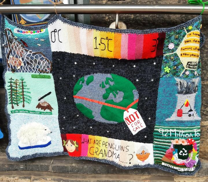 """A knitted panel with an earth in the centre, circled by a ribbon and tag saying """"not for sale"""". Various images associated with the climate crises border it."""