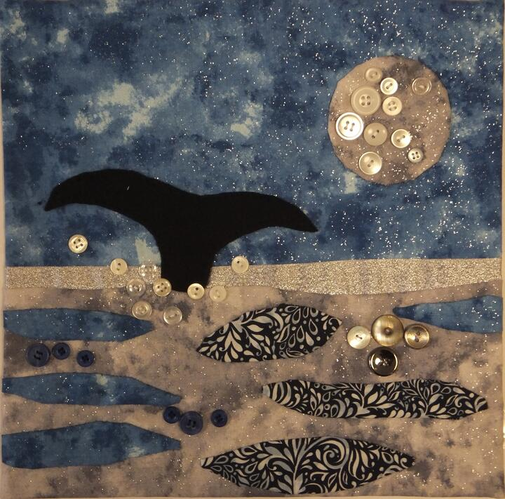 A glittery appliqued panel of a whale tail splashing up through an ocean underneath a moon, the moon and ocean spray are highlighted with pearlescent buttons.