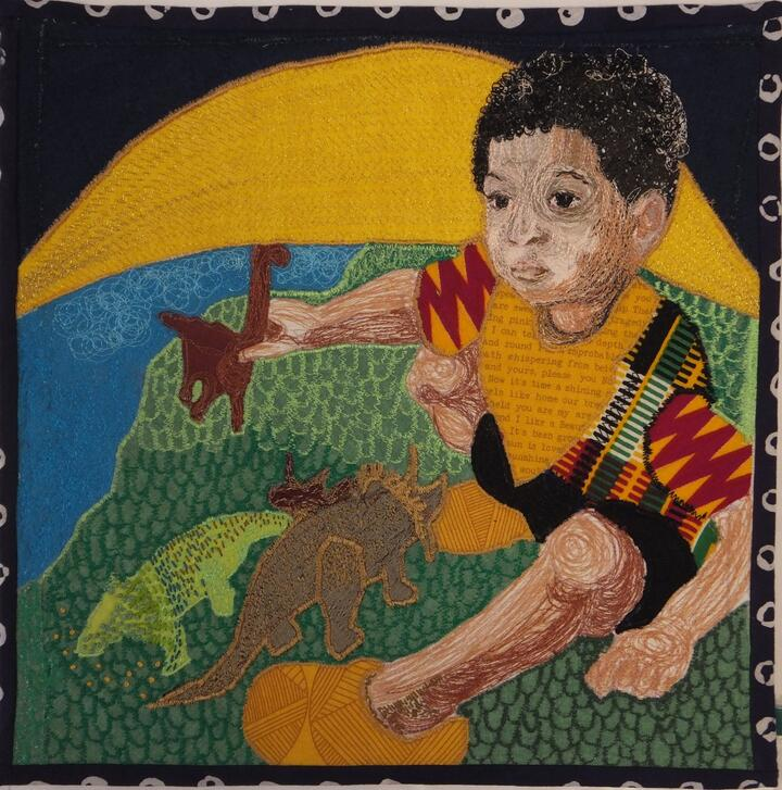 A machine embroidered and appliqued panel shows little boy with brown skin and black curly hair sitting on the earth, playing with dinosaurs. The sun is rising directly behind him.