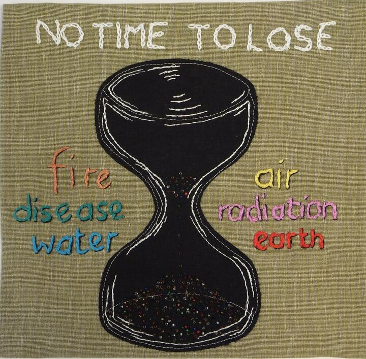"""An appliqued panel with a sandtimer in the centre, beads trickling through the sandtimer. In embroidered letters above the time it says """"No Time To Lose"""". To the left of the time it says """"fire, disease, water"""". To the right """"air, radiation, earth"""","""